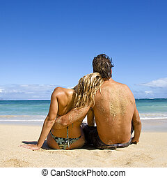 Attractive couple - Rear view of couple sitting on Maui,...