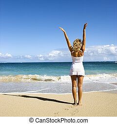 Woman with arms raised. - Pretty young woman standing on...