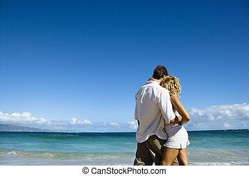 Intimate moment - Attractive couple in embrace on Maui,...