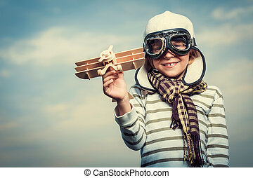 Aviator - Pilot with plane on a background of the sky