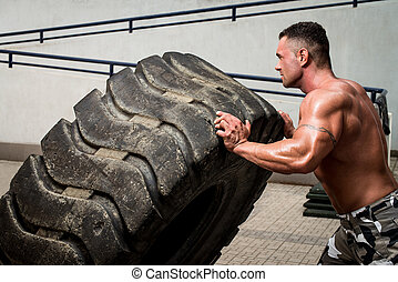 Crossfit training - Muscular Man with Truck Tire doing...