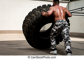 Turning Tires - Muscular Man with Truck Tire doing crossfit...