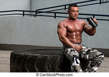 Bodybuilder with Protein Shake - Man Holding And Drinking...