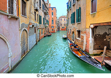 Gondola on small canal in Venice, Italy. - Gondola floats on...