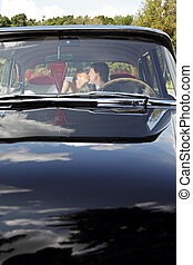Car with kissing bride and groom