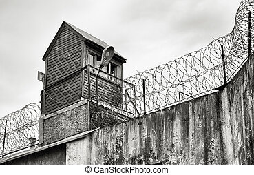 Old prison in black and white - Guard tower and barbed wire...