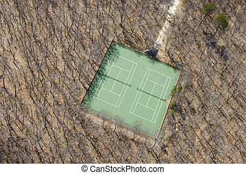 Tennis court. - Aerial view of tennis court in bare wooded...
