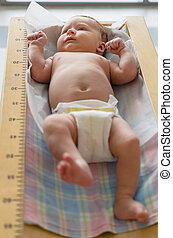 Cute baby lying in height meter in a clinic