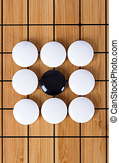Go Game - Black stone standing out from white pieces on...