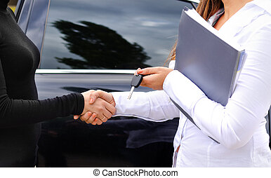 Clinching the purchase of a car and shaking hands - The...