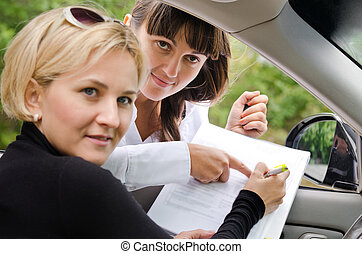Saleslady assisting a customer to buy a car