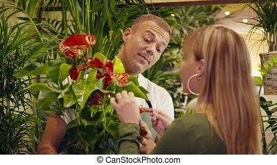 man in flower shop selling plant - mid adult man working as...