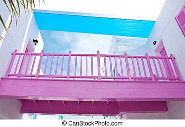 Pink wooden bridge with white mediterranean building