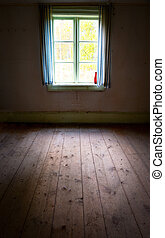 Light coming through window in empty room in old wooden...