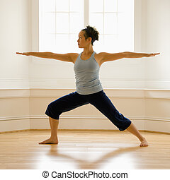 Woman in warrior pose - Young woman doing yoga warrior pose...