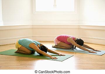 Yoga class women - Two young women on yoga mats doing...