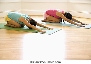 Women in yoga workout - Two young women on yoga mats doing...
