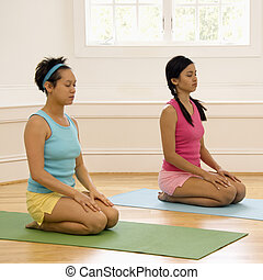 Women meditating - Two young women sitting on yoga mats with...