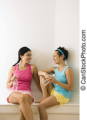 Workout friends taking break - Two young women in fitness...