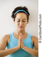 Woman meditating - Young woman holding hands in prayer...
