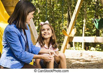Woman bandaging scrape - Hispanic girl sitting on playground...