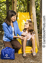 Mother with first aid - Hispanic girl sitting on playground...
