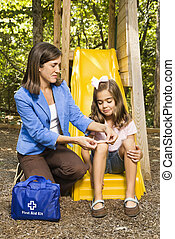 Mom bandaging scrape - Hispanic girl sitting on playground...