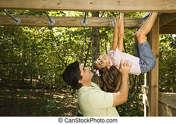 Father and daughter - Hispanic girl hanging by arms and legs...