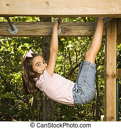 Girl on monkey bars. - Side view of Hispanic girl hanging by...