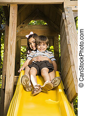 Kids on slide - Hispanic girl hugging boy on top of slide...