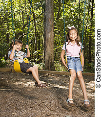 Kids on swing set - Hispanic boy and girl on swing set...