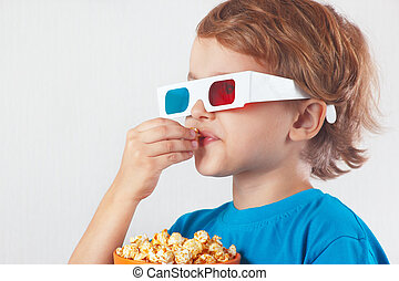 Young ironic boy in 3D glasses eating popcorn on white...