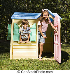 Kids in playhouse - Hispanic boy and girl in outdoor...
