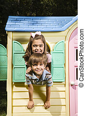 Kids in playhouse - Hispanic boy and girl posing in window...