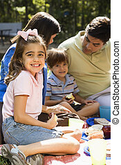 Family picnic - Hispanic girl smiling at viewer with family...