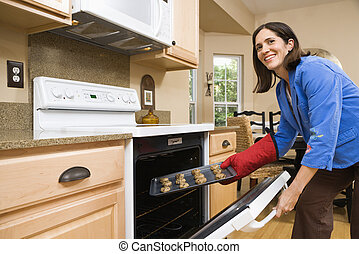 Woman baking cookies. - Hispanic mid adult woman putting...