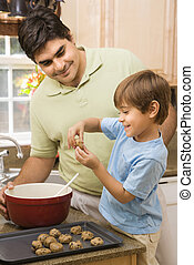 Dad and son making cookies. - Hispanic father and son in...