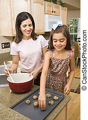 Mom and daughter. - Hispanic mother and daughter in kitchen...