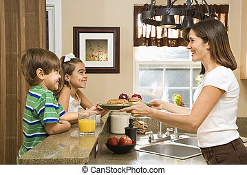 Mom giving kids breakfast. - Hispanic mother handing healthy...