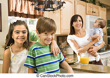 Family in kitchen. - Hispanic mother and children smiling at...