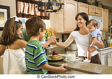 Mom giving kids breakfast - Hispanic family in kitchen with...