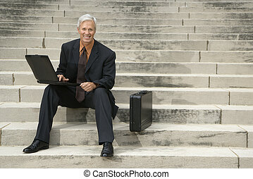 Businessman on steps - Caucasian middle aged businessman...