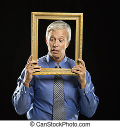 Man holding picture frame. - Caucasian middle aged...