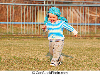 Full length of happy little boy running in garden with mouth open