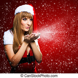 Portrait of a young Santa girl blowing stars