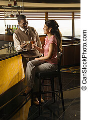 Couple toasting drinks - Mid adult African American man...