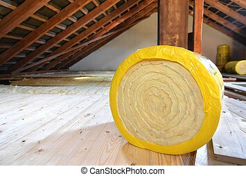Loft Insulation - A roll of insulating glass wool on an...