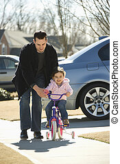 Father and daughter - Caucasian father helping daughter ride...