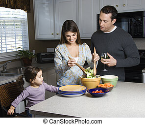 Family in kitchen. - Caucasian woman making salad on kitchen...