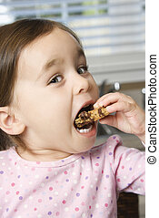 Girl eating cookie - Caucasian girl eating chocolate chip...